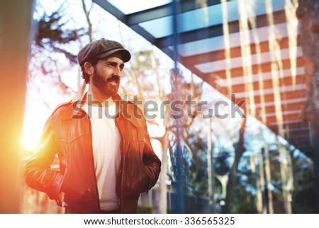 Half length portrait of a handsome man with trendy look with hands in pockets standing on the street, adult male dressed in stylish retro clothes waiting for someone in urban setting  - stock photo
