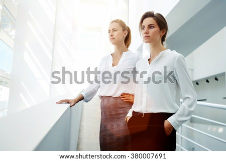 Half length portrait of a two female managing directors resting in hallway after successful presentation, young businesswomen concentrated looking in window while standing in modern office interior  - stock photo