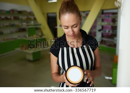 Half length portrait of a young charming woman consultant holding plastic jar with copy space for your brand, pretty female seller reads the information content of a cosmetic product during work day  - stock photo