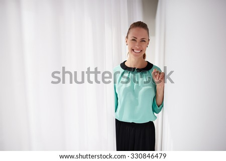 Half length portrait of a young cheerful successful businesswoman dressed in classic elegant clothes posing, female service worker with beautiful smile standing in modern interior, copy space area - stock photo