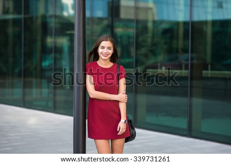 Half length portrait of a young cheerful successful businesswoman dressed in classic elegant clothes posing, female entrepreneur with beautiful smile standing outdoors against modern office building  - stock photo