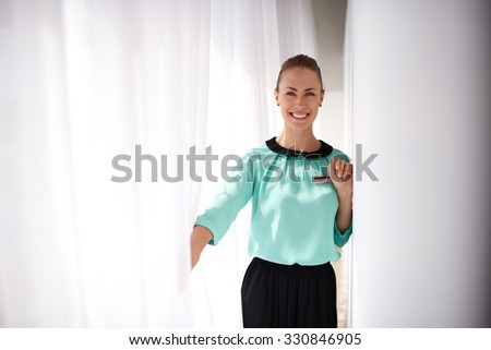 Half length portrait of a young happy woman seller dressed in elegant clothes posing during her recreation time, female service worker with beautiful smile standing in modern interior, copy space area - stock photo