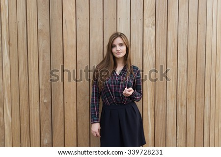 Half length portrait of a young lady with cute face posing for the camera against wooden wall, gorgeous hipster girl with trendy look looking at you while standing on copy space area background - stock photo