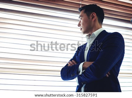 Half length portrait of a young serious men entrepreneur dressed in luxury clothes with crossed arms standing near office window, managing director thinking about something before business meeting  - stock photo