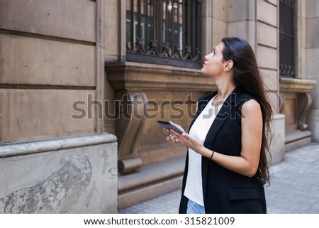 Half length portrait of a young woman tourist using touch pad for navigation while lost the way during walking, attractive female looking at city map on her digital tablet computer during strolling - stock photo