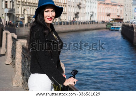 Half length portrait of an attractive Caucasian brunette standing on the background of beautiful river and enjoying her vacation holidays, young female model having good time during stroll in the city - stock photo