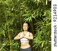 Half length portrait of Asian American woman in fitness attire standing in yoga position in bamboo forest in Maui, Hawaii. - stock photo