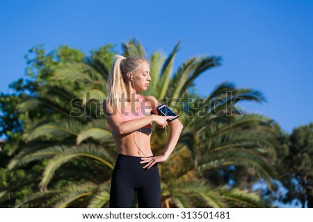 Half length portrait of athletic female touching screen of smart phone in running armband while listening music in headphones, fit woman taking break after workout outdoors in sunny summer day - stock photo