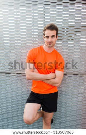 Half length portrait of attractive caucasian man posing on metal fence while resting after active workout training at early morning outdoors,male runner with arms crossed posing against copy pace area - stock photo