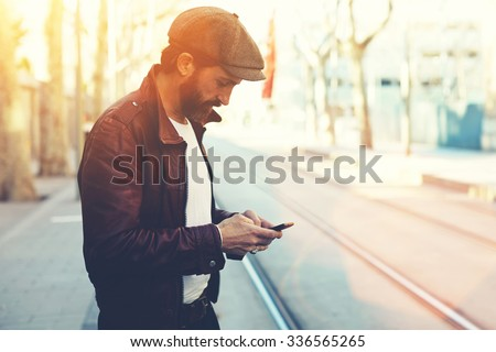 Half length portrait of bearded male with retro style using cell telephone while standing in urban setting, man dressed in stylish clothes chatting on smart phone during walking in cool spring day  - stock photo