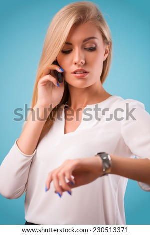 Half-length portrait of beautiful business lady wearing white classic blouse and black skirt looking at her watch having a phone conversation thinking about the meeting today. Isolated on blue - stock photo