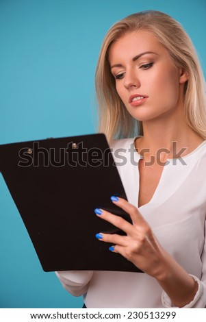 Half-length portrait of beautiful business lady wearing white classic blouse standing looking at the folder writing something in it. Isolated on blue background - stock photo