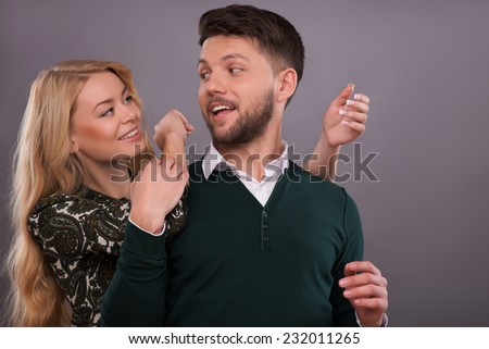 Half-length portrait of beautiful happy couple standing together hugging each other laughing speaking about their wedding. Isolated on dark background - stock photo