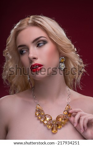 Half-length portrait of beautiful sexy blonde with red tempting lips and perfect skin wearing great jewelry showing us her necklace isolated on dark background - stock photo