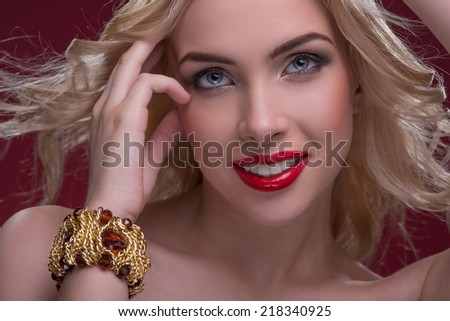 Half-length portrait of beautiful sexy smiling blonde with red tempting lips and perfect skin wearing precious golden bracelet dancing touching her hair isolated on dark background - stock photo