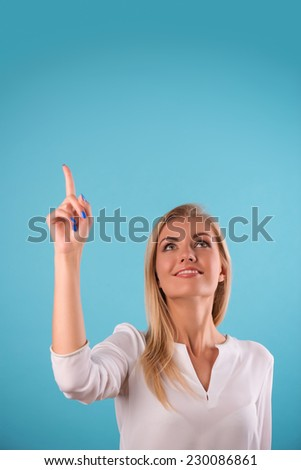 Half-length portrait of beautiful smiling blonde wearing white classic blouse standing pointing at something looking up. Isolated on blue background - stock photo