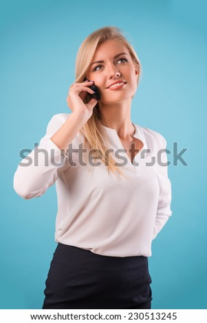 Half-length portrait of beautiful smiling business lady wearing white classic blouse and black skirt standing having a phone conversation with her boyfriend. Isolated on blue background - stock photo