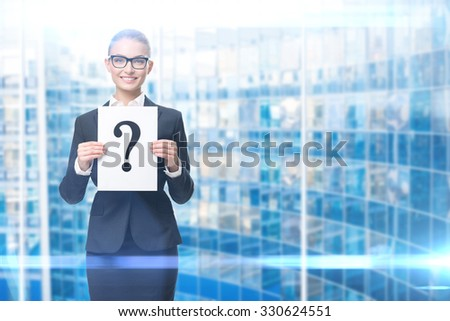 Half-length portrait of business woman handing question mark, blue background. Concept of problem and solution - stock photo