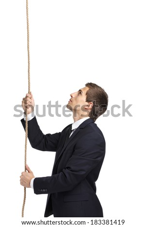 Half-length portrait of businessman swarming up the rope, isolated on white. Concept of job promotion and hard work