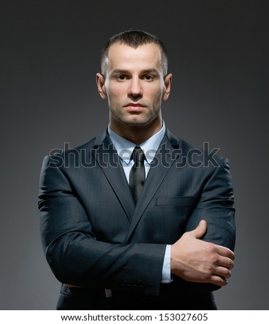 Half-length portrait of businessman wearing business suit and black tie with arms crossed - stock photo