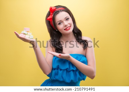 Half-length portrait of charming smiling dark-haired woman wearing nice red headband and wonderful blue dress showing us her favorite delicious colorful fruit drops. Isolated on yellow background - stock photo
