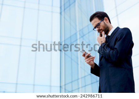 Half length portrait of confident young business man holding mobile phone with another hand against his mouth - stock photo