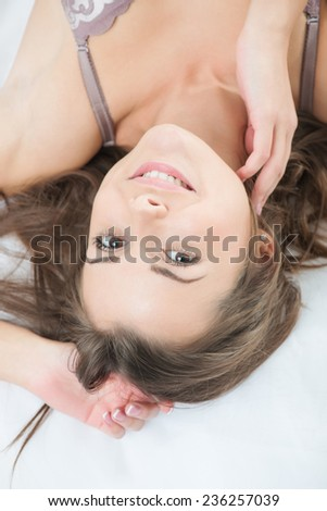 Half-length portrait of dark-haired beautiful smiling girl wearing sexy lingerie lying in the bed waking up in the morning. Top view - stock photo