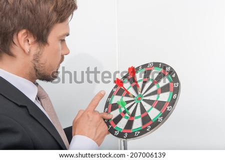 Half-length portrait of dark-haired man wearing black jacket looking at the target in his hands and counting how many points he has - stock photo