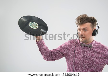 Half-length portrait of excited young DJ with stylish haircut with headphone posing with vinyl record isolated on white background