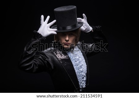 Half-length portrait of fair-haired matchless juggler wearing interesting black costume and white shirt standing with great black top on his head for performance. Isolated on black background - stock photo