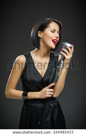 Half-length portrait of female singer with closed eyes wearing black evening dress and keeping mic on grey background. Concept of music and retro fashion
