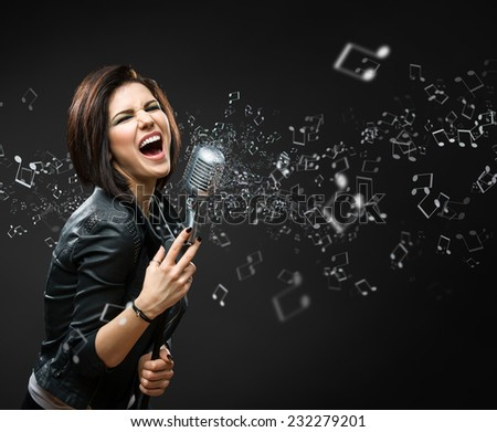 Half-length portrait of female singing rock musician keeping mike on grey background - stock photo