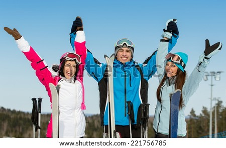 Half-length portrait of group of alps skier friends with hands up. Concept of cute winter sport and funny vacations with friends - stock photo
