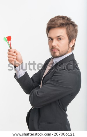 Half-length portrait of handsome dark-haired bearded man wearing great black jacket holding darts in his hands and thinking about his last win. Isolated on white background - stock photo