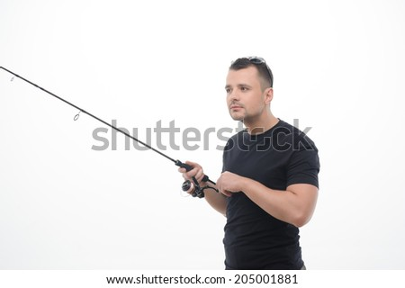 Half-length portrait of handsome fisherman wearing black T-shirt concentrated on his favorite hobby. Isolated on the white background - stock photo