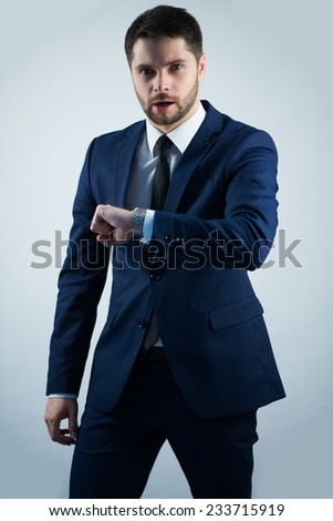 Half-length portrait of handsome young bearded busy man wearing white shirt tie and blue jacket looking at his watch noticed that he is late. Isolated on white background - stock photo