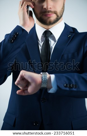 Half-length portrait of handsome young bearded busy man wearing white shirt tie and blue jacket calling his subordinate and looking at his watch. Isolated on white background - stock photo