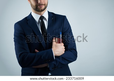 Half-length portrait of handsome young bearded smiling man wearing white shirt tie and blue jacket holding his dairy. Isolated on white background - stock photo