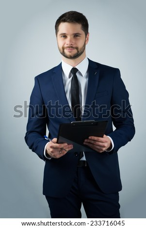 Half-length portrait of handsome young bearded smiling man wearing white shirt tie and blue suit holding the black folder looking at us. Isolated on white background - stock photo