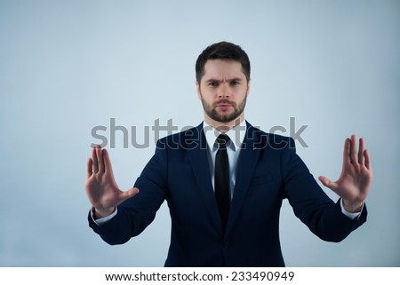 Half-length portrait of handsome young bearded thoughtful man wearing white shirt tie and blue jacket standing  asking us to stop. Isolated on white background - stock photo