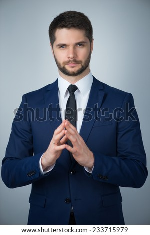 Half-length portrait of handsome young man wearing white shirt tie and blue suit standing thinking hard about something. Isolated on white background - stock photo