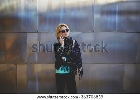 Half length portrait of hipster girl using cellphone for call to the friend while standing outdoors, young casually-dressed woman having mobile phone conversation while waiting for someone outside - stock photo