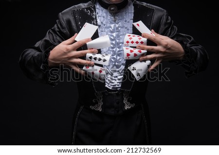 Half-length portrait of juggler wearing interesting black costume and white shirt holding cards between his fingers. Isolated on black background