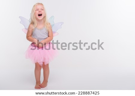 Half-length portrait of little fair-haired lovely crying girl wearing pretty grey vest and pink skirt putting her hands on the waist closed her eyes - stock photo