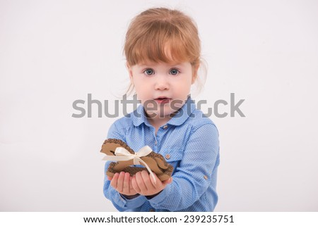 Half-length portrait of little lovely smiling girl wearing blue shirt and brown pants holding in her hands little wooden horse. Isolated on the white background - stock photo
