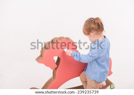 Half-length portrait of little lovely smiling girl wearing blue shirt and brown pants standing back climbing up on the pink wooden toy horse. Isolated on the white background - stock photo