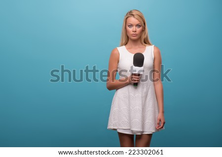 Half-length portrait of lovely fair-haired serious TV presenter wearing pretty white dress standing holding a microphone. Isolated on blue background - stock photo