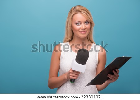 Half-length portrait of lovely fair-haired TV presenter wearing pretty white dress standing to us holding a microphone holding a folder. Isolated on blue background - stock photo