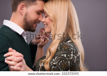 Half-length portrait of lovely happy smiling couple standing with closed eyes facing each other dancing enjoying the moment they are together. Isolated on dark background - stock photo