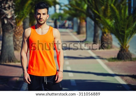 Half length portrait of muscular build handsome male posing for the camera outdoors, handsome runner in bright t-shirt resting after workout, copy space area for your text message or advertise content - stock photo